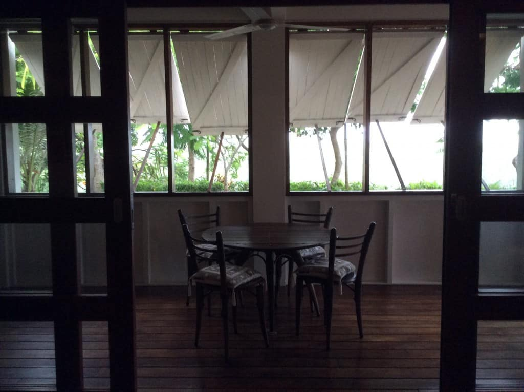 The main house lower level is protected by a wrap-around veranda. Wooden shutters keep the elements at bay from the interior glass and screen openings.