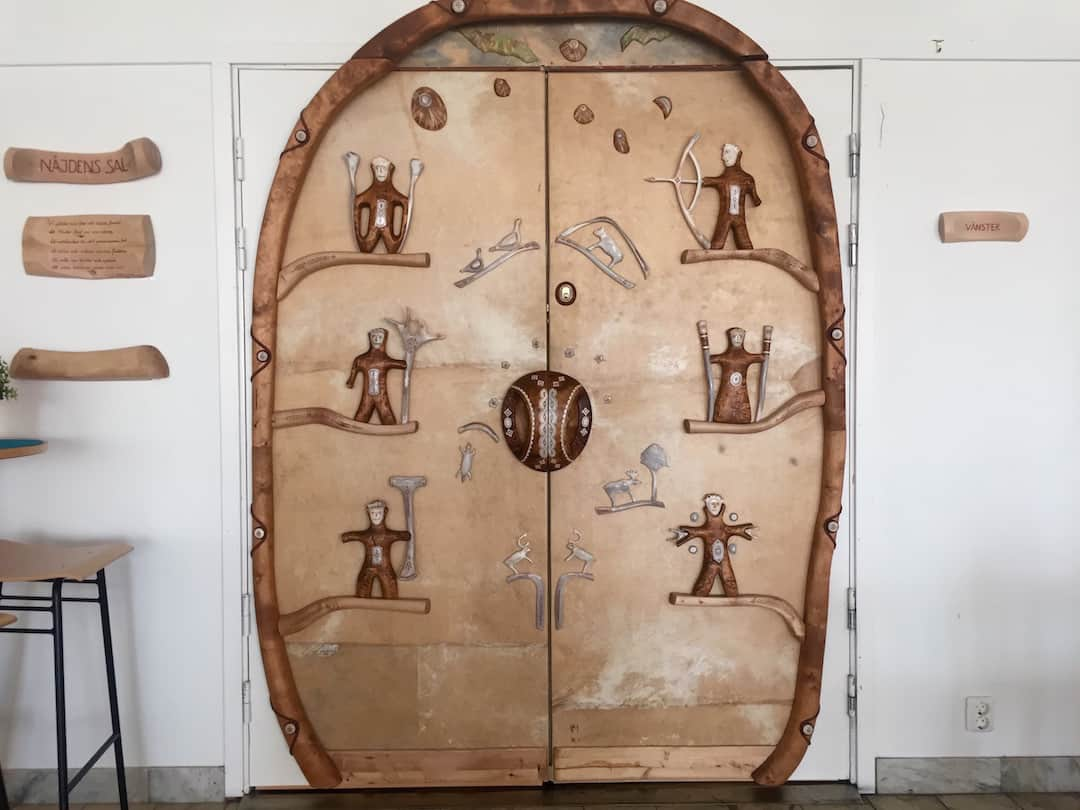 Traditional Sami carved motifs decorate a door at the Kiruna Visitors Center