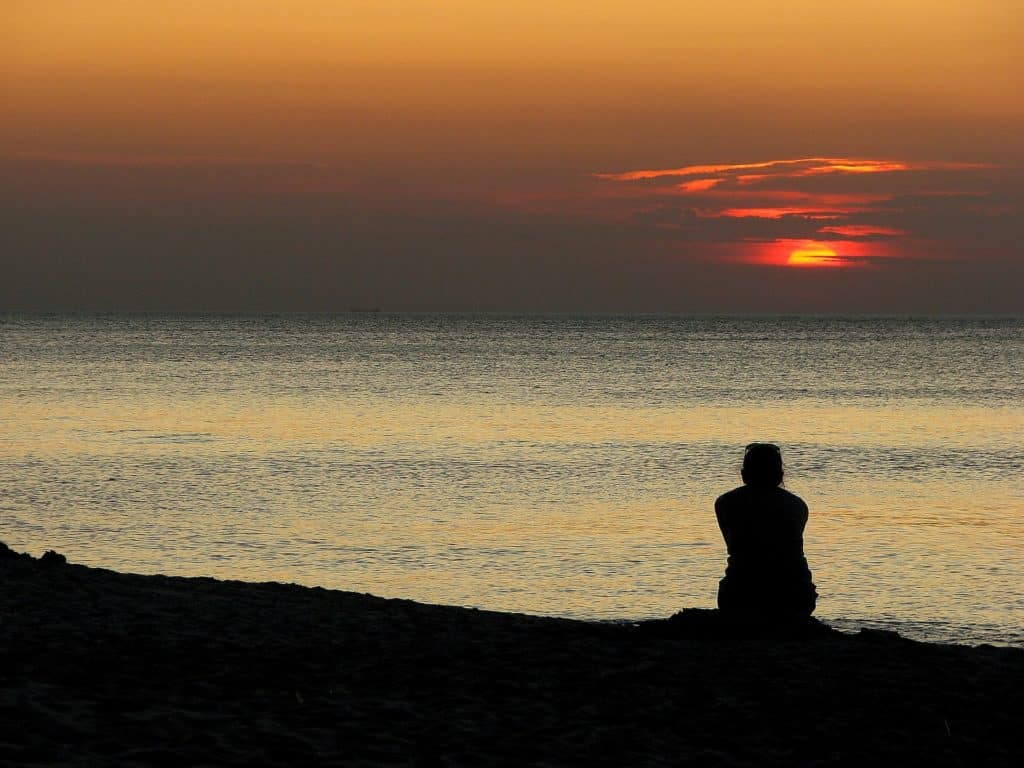 silhouette of traveler gazing at sunset over the sea