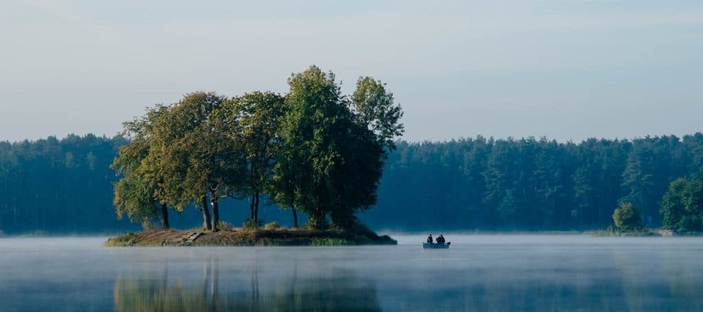 misty lake with fisherman and island